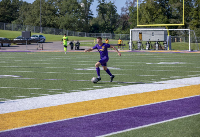 a Bethel athlete player dribbles the soccer ball during a match