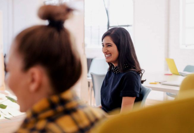 a girl laughs in a meeting with other students