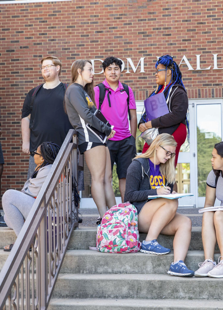 students gather on steps outside of class