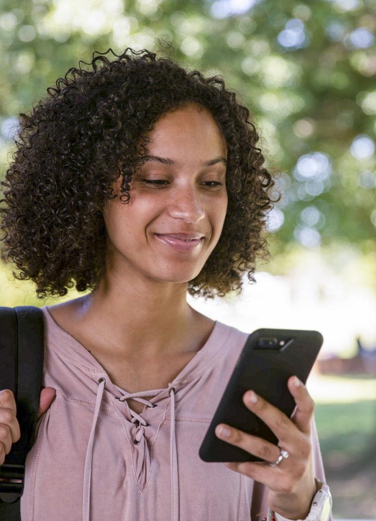 a female student looks at her phone outdoors