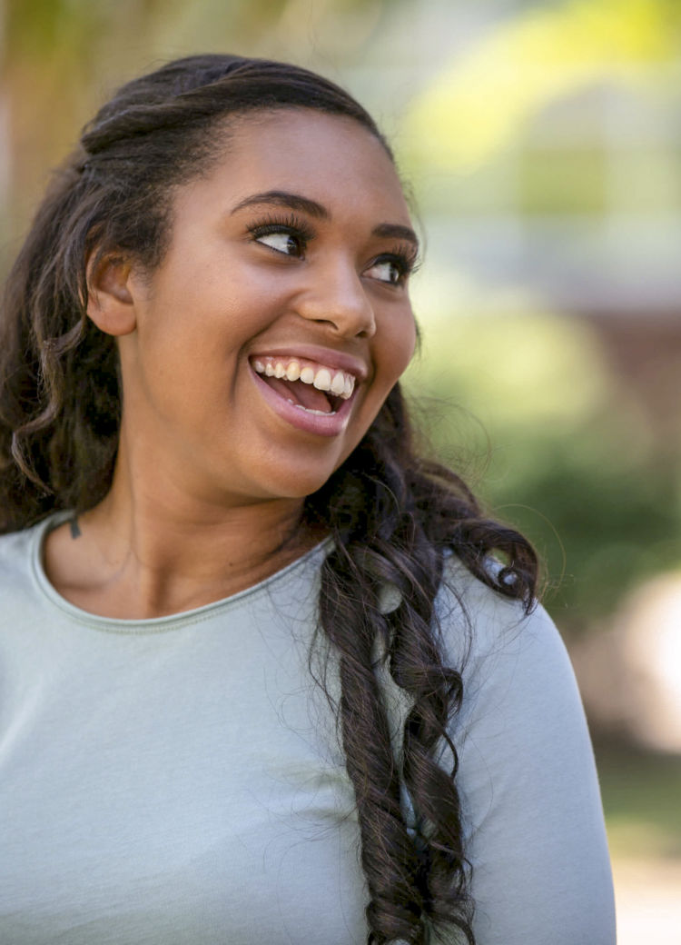 a female student smiles and looks off-camera in an outdoor portrait