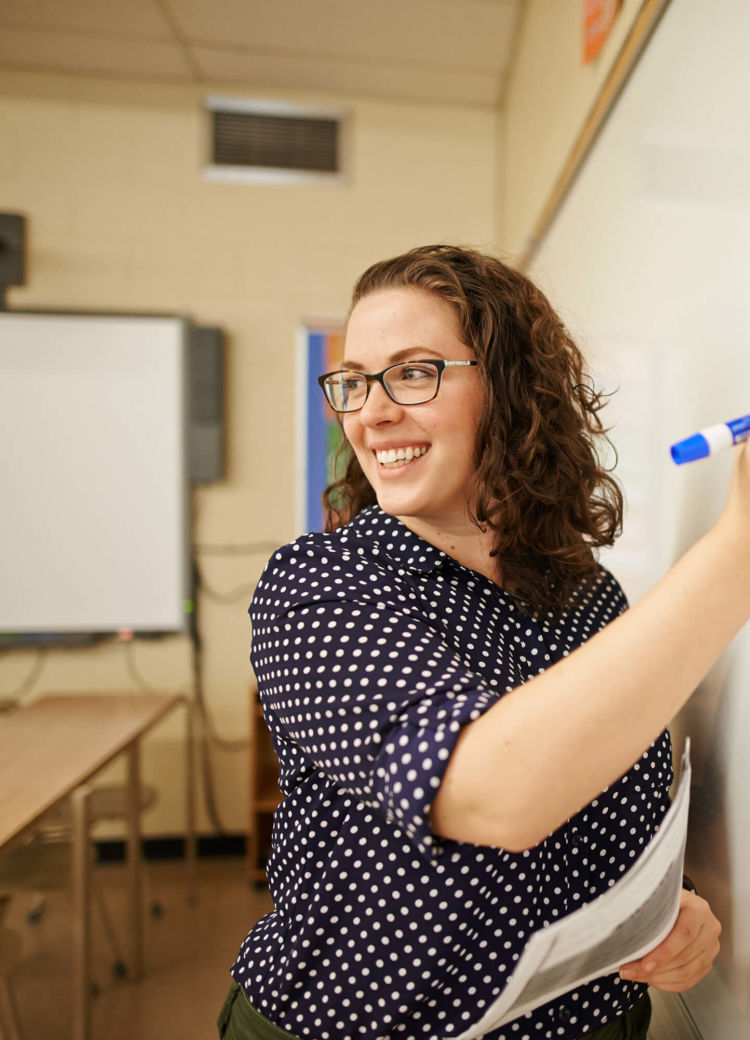 a teacher leads class while working on the whiteboard