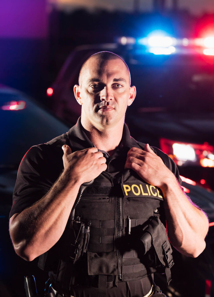 an officer stands in front of two police cars with lights flashing