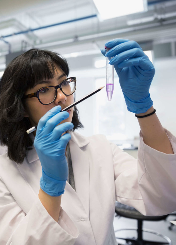 a female student examines a substance in a chemistry lab
