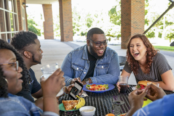 students laugh while eating lunch outside