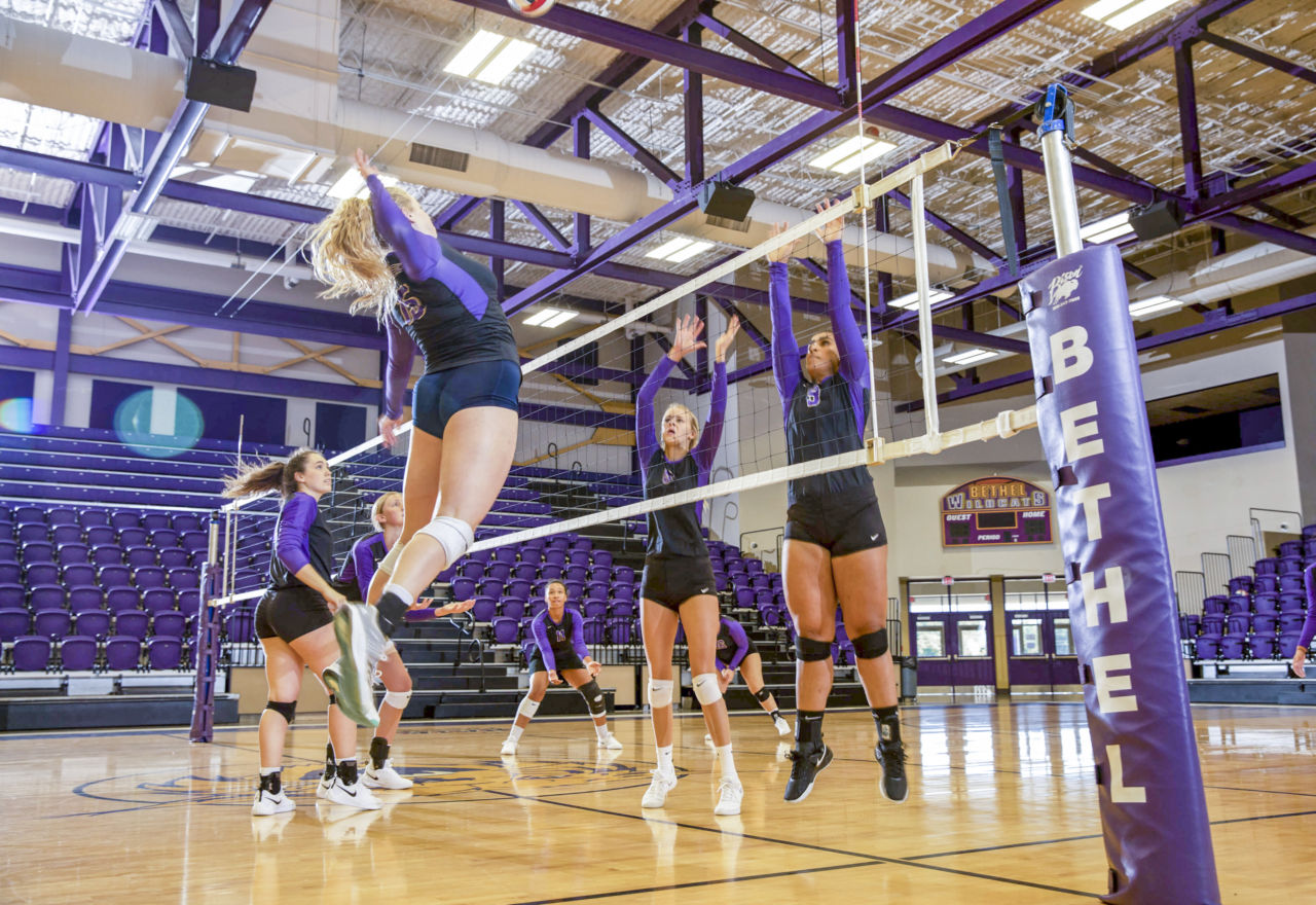 a volleyball player jumps in the air to spike the ball