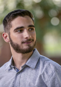 a male student looks of camera during an outdoor portrait