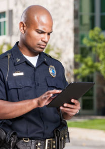 an officer uses a tablet in a parking lot