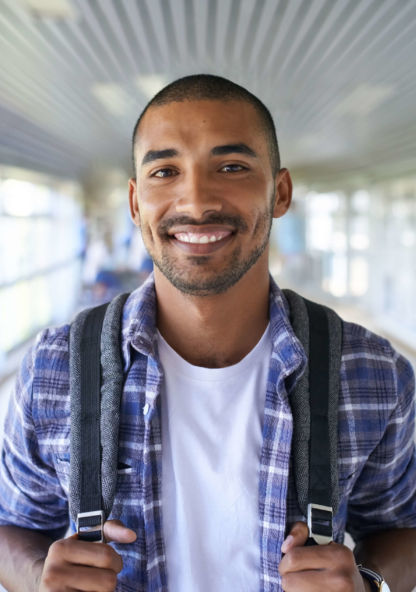 a student smiles for a portrait with his backpack