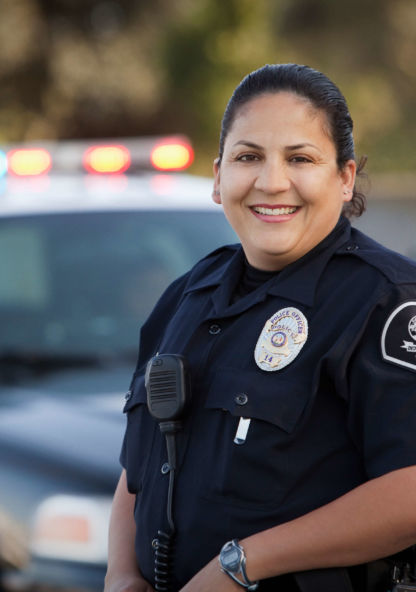 an officer stands in front of a police vehicle