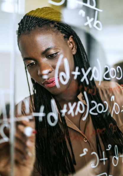 a student uses a glass wall to solve a mathematical equation