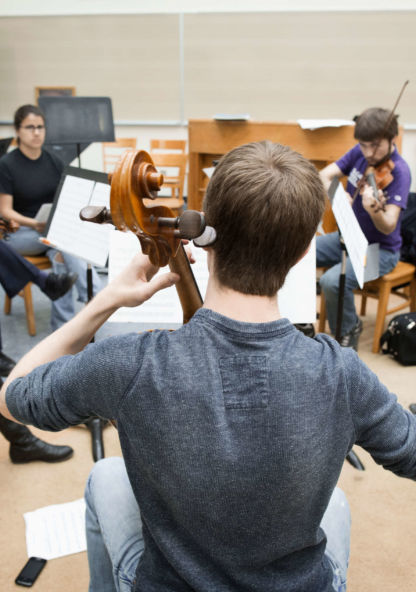 a group of musicians rehearse in a circle